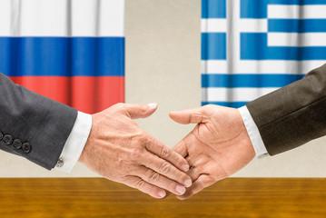 Vertreter Russlands und Griechenlands reichen sich die Hand