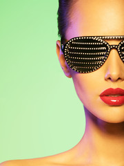 Fashion portrait of  woman wearing black sunglasses with strass.