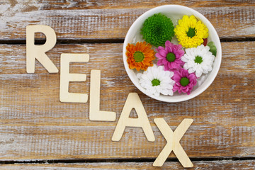 Relax written with wooden letters and santini flowers