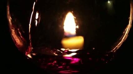 Bicchiere con candela e vino rosso versato