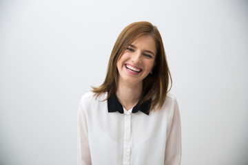 Portrait of a laughing young business woman over gray background