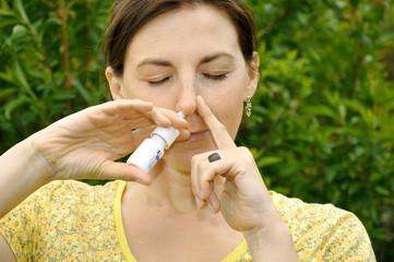 Frau mit Erkältung benutzt Nasenspray
