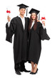 Young couple posing with their diplomas