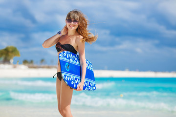 Beautiful woman on a tropical beach with a Board for swimming.