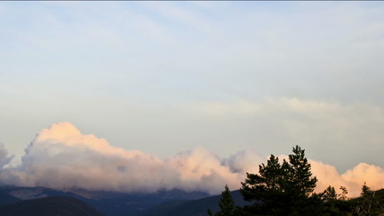 Awesome clouds rolling over ridge of mountain