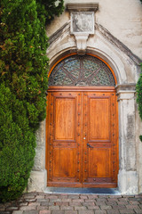 Ancient wooden door in old stone wall with plant in  Switzerland