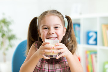 little girl drinking milk from glass indoor