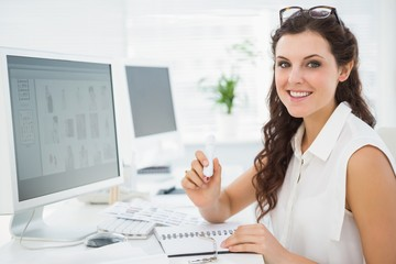 Portrait of smiling businesswoman writing on notebook