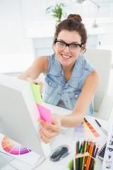 Smiling casual designer using colour wheel