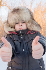 Boy in the winter hat shows gesture all is well