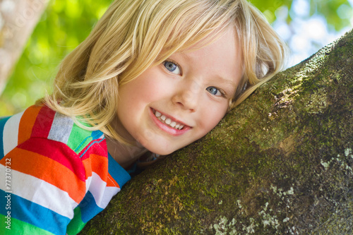 Cute happy child relaxing outdoors in tree - 77370732
