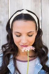 Pretty hipster smelling a flower