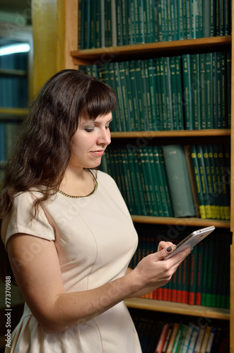 A woman with a gadget in the library Poster