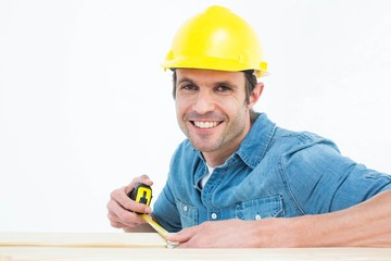 Male carpenter using measue tape