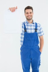 Smiling male repairman showing clipboard