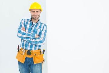 Confident repairman leaning on blank billboard