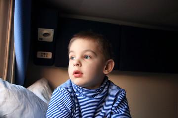 Мальчик смотрит в окно поезда в купе