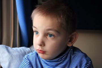 Мальчик серьезно смотрит в окно поезда в купе