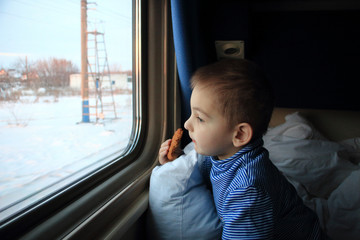 The boy looks out the window of the train compartment