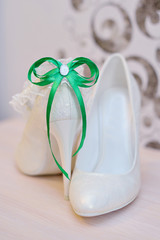 Elegant bridal shoes and a white garter
