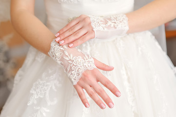 Wedding gloves on hands of the bride