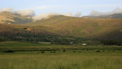 Clouds rolling over ridge of mountain above ranch