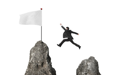 businessman jumping over mountain peak to blank white flag