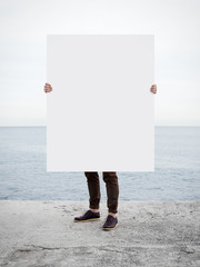 Man with blank poster on sea background