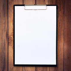 white paper clipboard on wood background and texture
