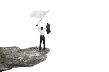 A businessman cheering on cliff waving flag with white backgroun