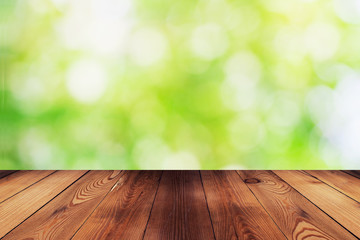 Wood table and bokeh abstract nature green background