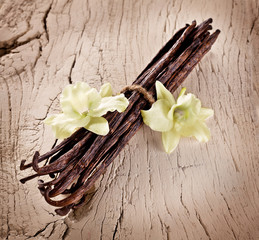Bunch of vanilla sticks and flowers on old wood.