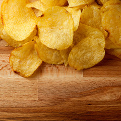 Top view potato chips over wooden table