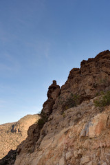 Rocky cliff with blue sky, Jabal Nakhal, Sultanate of Oman