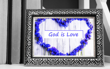 Text God is Love in frame standing on shelf at home