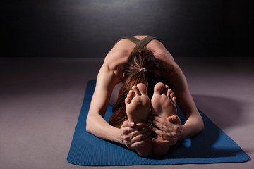 Mature woman practicing yoga on the floor