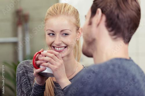 frau mit einer tasse kaffee unterhält sich mit ihrem freund - 77378139