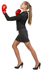 Businesswoman wearing boxing gloves punching