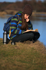 Young girl sitting on the ground and relaxing with book