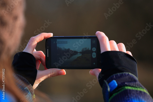 Young girl use her mobile for making photo - 77378922