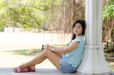 Asian woman portriat sitting  smiling in the park