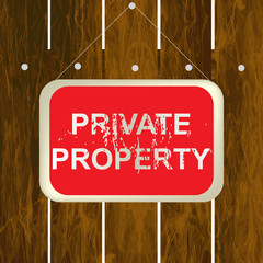 PRIVATE PROPERTY sign hanging on a wooden fence