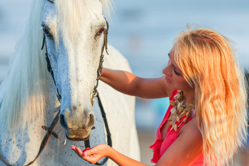 Young woman feeding a horse