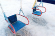 snow covered swing and slide at playground in winter - 77381538