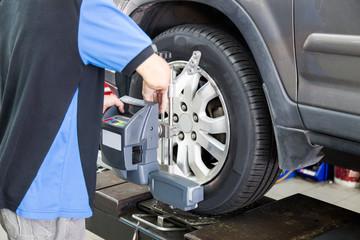 Mechanics adjusting equipment during wheel alignment on vehicle