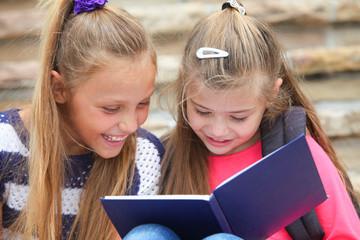 schoolgirls reading a book outdoors