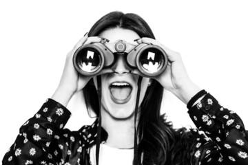 Surprised girl looking through binoculars black and white