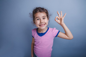 girl child 6 years of European appearance showing thumbs up ok o