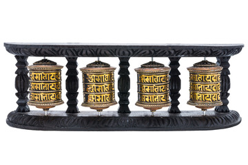 4 prayer wheels in the wooden pillars with white background