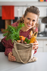 Portrait of smiling housewife with vegetables from local market